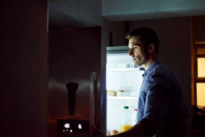 man looking in refrigerator at night