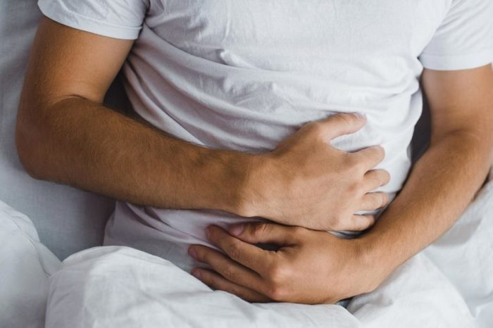 Man holding his stomach as if having abdominal cramps.
