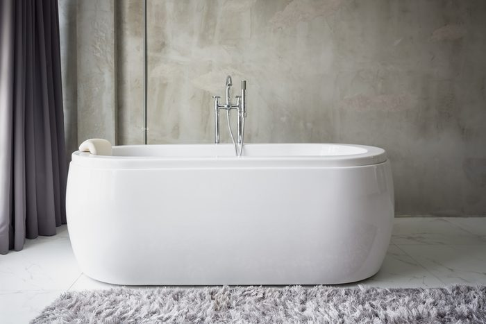 Big white bathtub in a middle of industrial loft bathroom style with grunge cement wall.