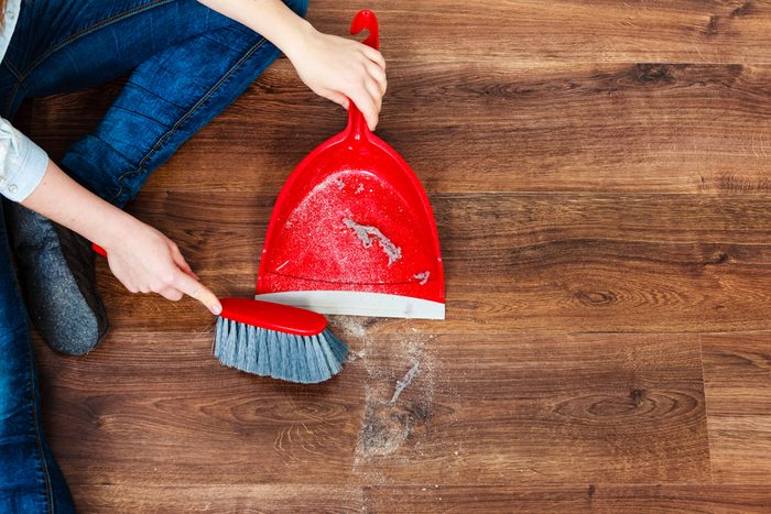 Cleanup housework concept. Closeup cleaning woman sweeping wooden floor with red small whisk broom and dustpan indoor