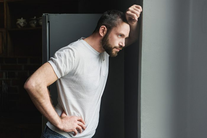 side view of depressed young man leaning on wall and looking away