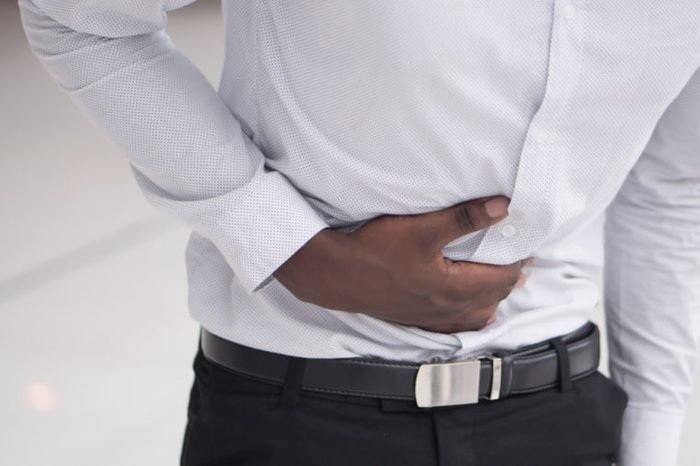 A man holding his stomach as if having a stomachache.
