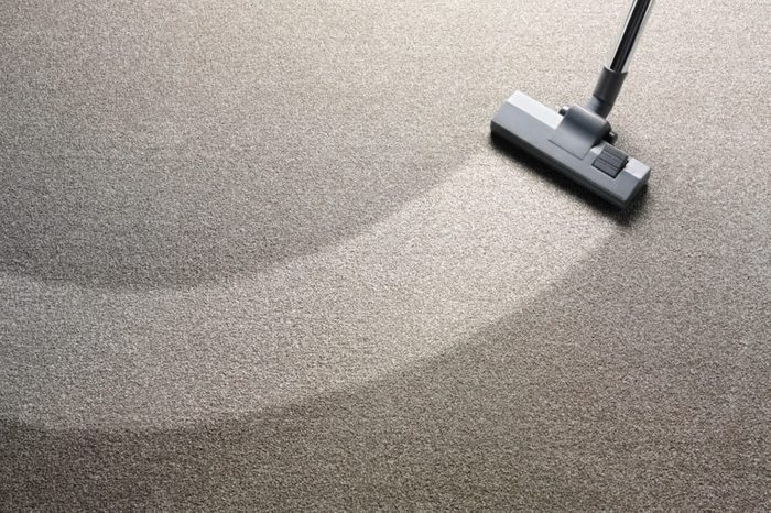 Vacuum cleaner on a carpet with an extra clean strip for copy space