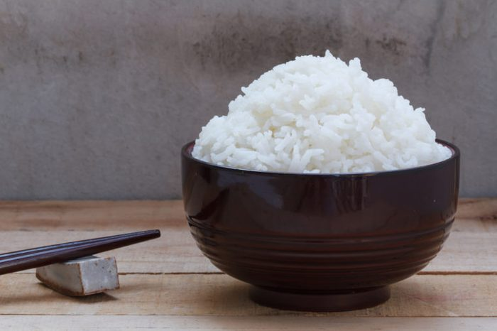 Cooked rice in bowl on wood background.