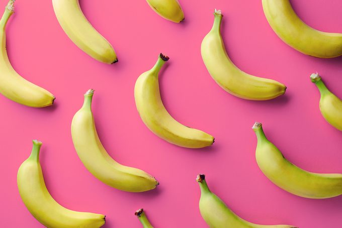 Colorful fruit pattern of fresh yellow bananas on pink background. From top view