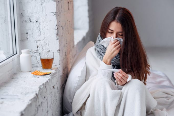 Cold and flu. Sick woman caught cold, feeling illness and sneezing in paper wipe. Closeup of beautiful unhealthy girl covered in blanket wiping nose and looking at thermometer. Healthcare concept.