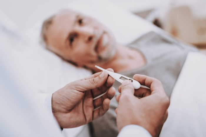Thermometer and Man. Old Man Lies in Hospital. Nurse and Doctor Help Patient. White Room and Patient. Therapy for Patient in a Clinic. Care Doctor and Nurse. Rehabilitation and Therapy for Patient