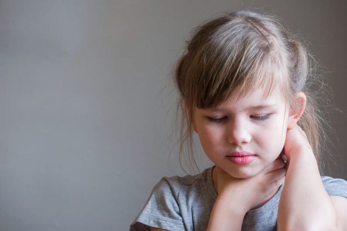 Neck pain. Portrait stressed unhappy child girl with back pain, Negative human emotions facial expression feeling.