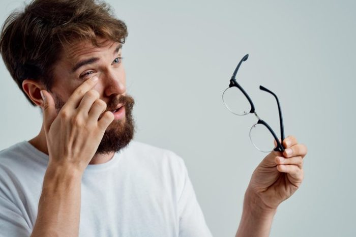 Bearded man rubbing his eye and holding his glasses.