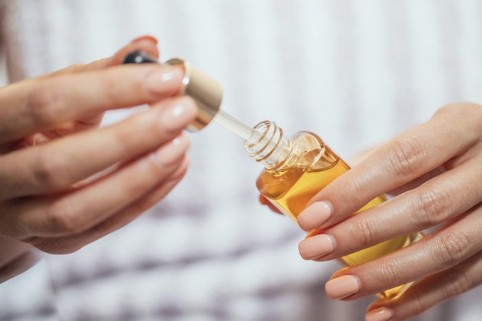 hands holding a dropper in a bottle of oil