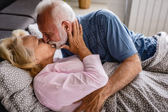 senior couple in bed kissing