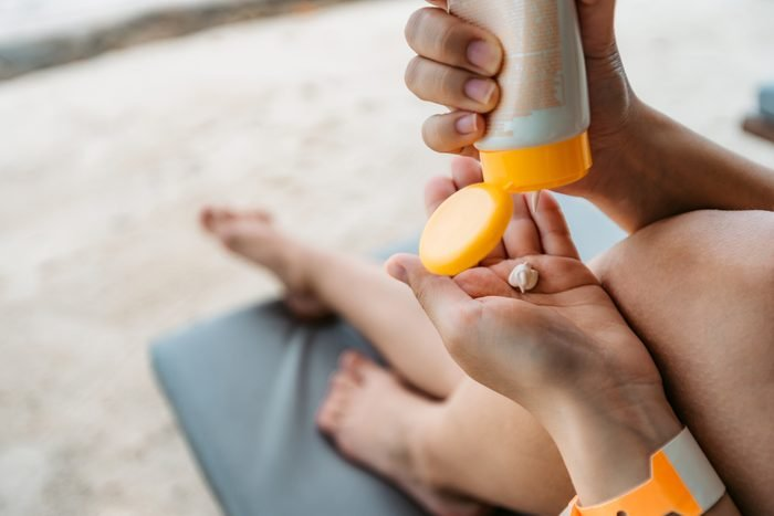 squeezing sunscreen lotion into hand