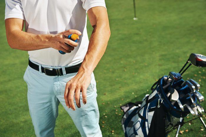 man applying sunscreen while playing golf