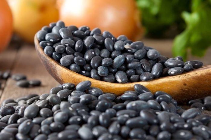 Black beans in a wooden spoon with cilantro and onions in the background