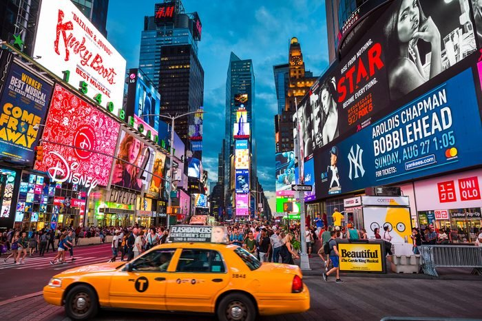 NEW YORK CITY - CIRCA AUGUST, 2018: A yellow taxi passes under the bright flashing lights of Broadway and tourist crowds of Times Square.