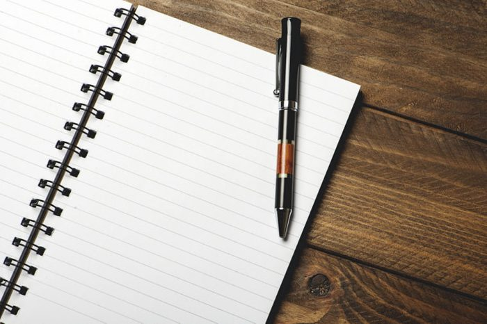 Ballpoint pen in a notebook on a brown background. Office.