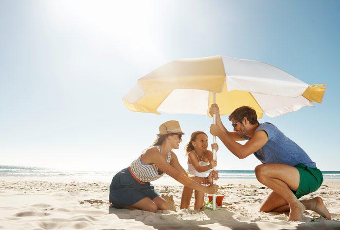 family setting up umbrella at beach