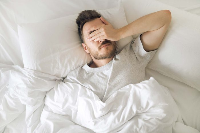 man in bed holding his hand over his eyes, exasperated