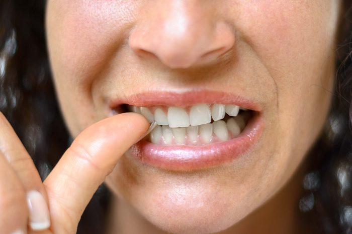 woman biting her thumbnail