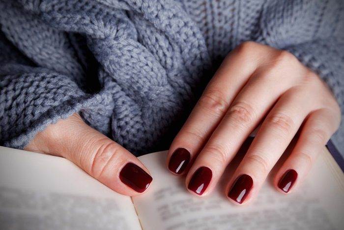 nicely manicured nails with dark red polish