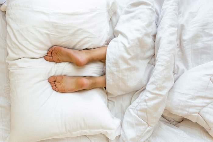 feet in bed sticking out from under the covers