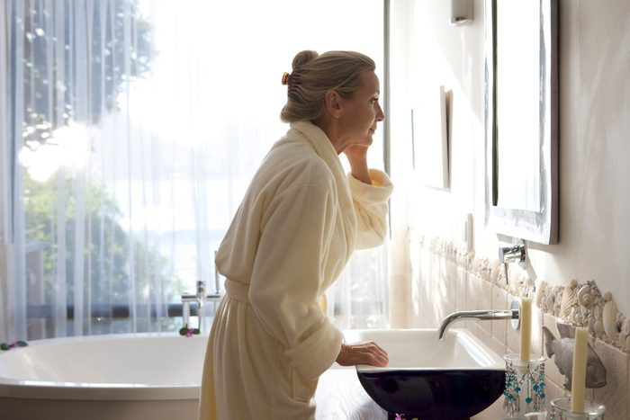 mature woman wearing a robe and looking in bathroom mirror