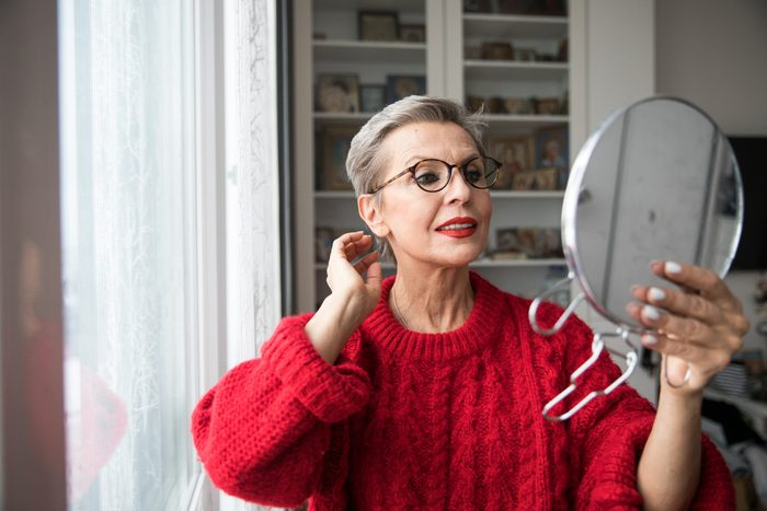 mature woman looking into hand held mirror