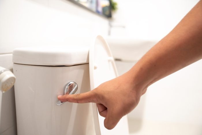 close up of hand flushing toilet