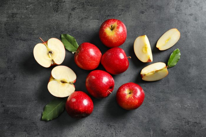 Fresh ripe red apples on grey background, top view