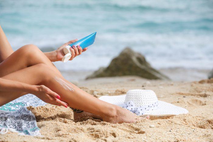 Girl applying sunscreen on her legs
