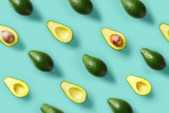 Avocado pattern on blue background. Pop art design, creative summer food concept. Green avocadoes, minimal flat lay style. Top view. Banner.