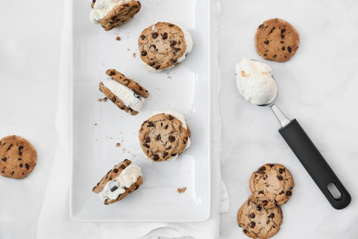Chocolate chip cookie vanilla ice cream sandwiches with cookie crumbles all around. Ice cream scoop on the side with other cookies on a marble table top. Summer snacks.