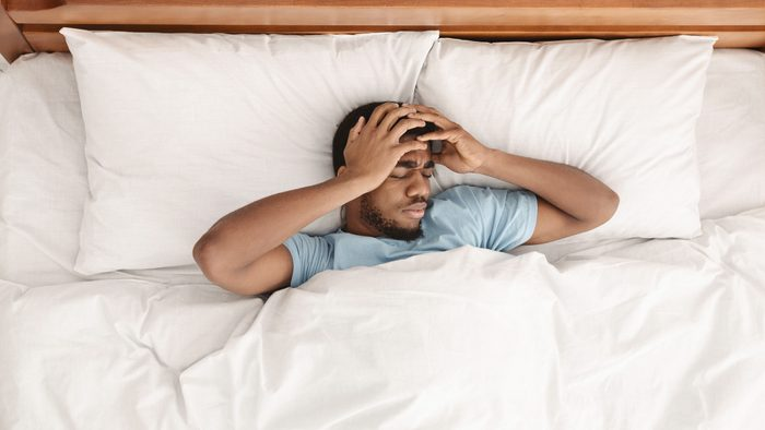 Restless african american man waking up with headache, lying in bed early in morning, top view