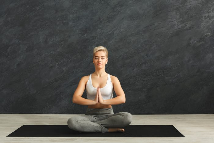 Fitness, woman yoga relax meditation in lotus pose in gym against grey background. Young slim girl makes exercise.