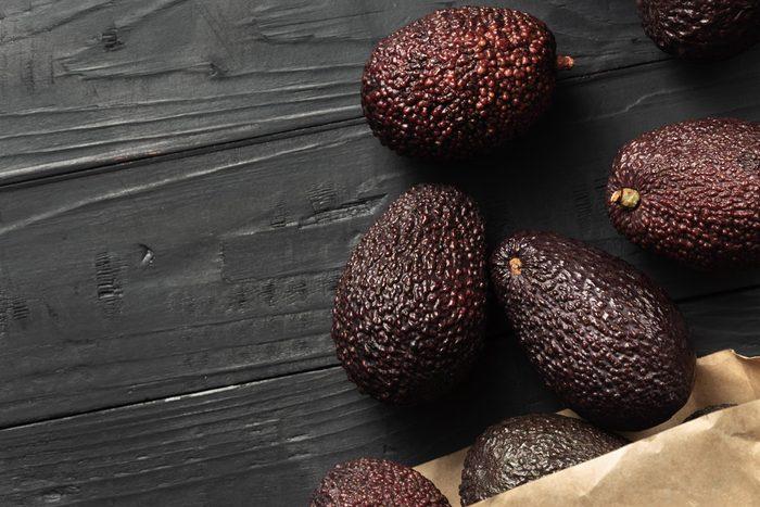 avocados on table and brown bag