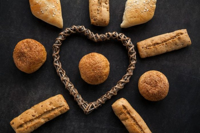 Concept of gluten free buns for allergic people with disease. Variation of bread with wooden heart shape on dark background.
