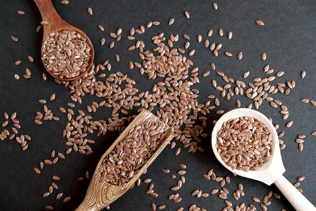 flaxseeds in spoons and on table