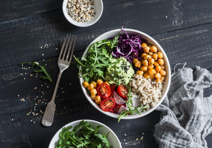 Quinoa and spicy chickpea vegetable vegetarian buddha bowl. Healthy food concept. On a dark background, top view