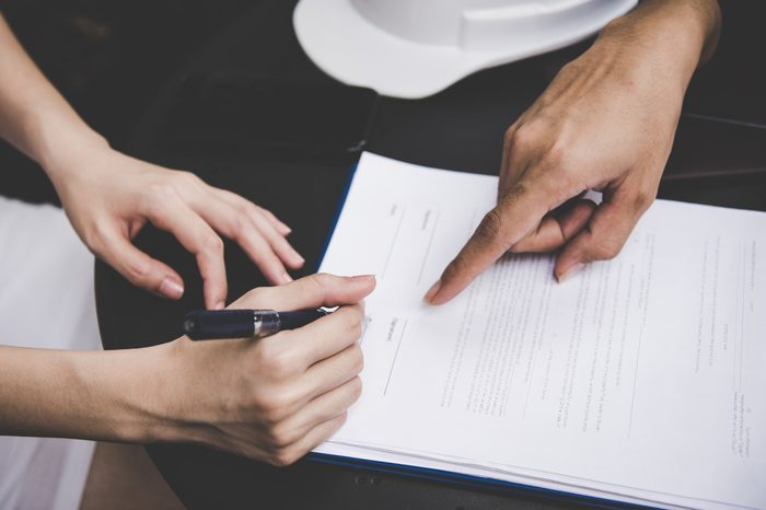 hands signing a contract