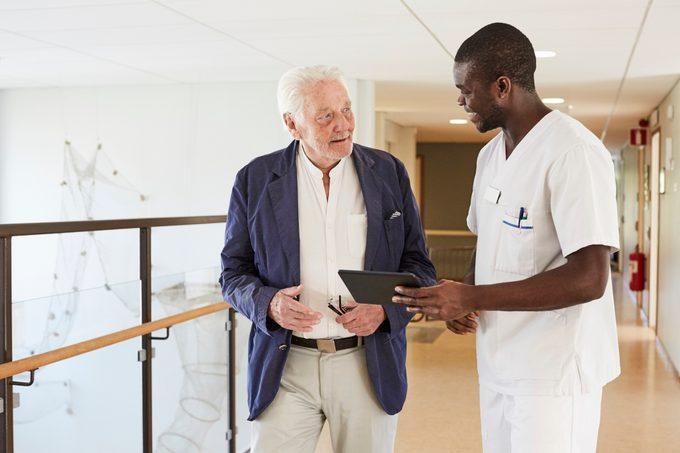 male nurse talking to senior male patient