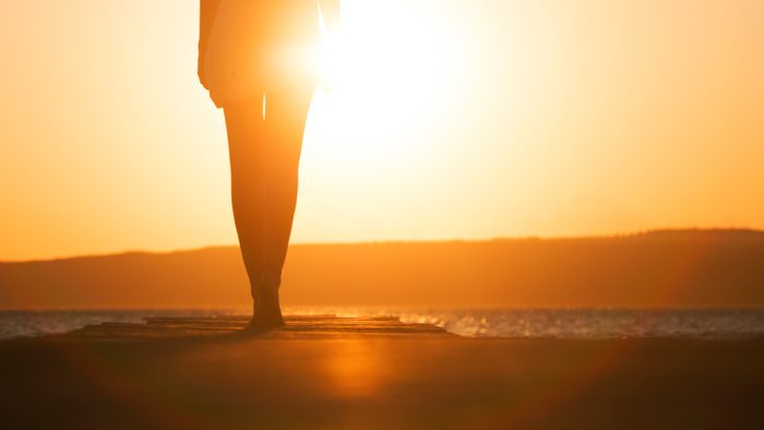 young woman's silhouette at sunset