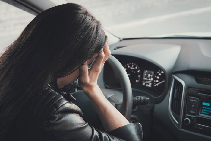 Stressed woman driver sitting inside her vehicle. Brunette girl doing face palm being at car wheel and dashboard background. Female driver is frustrated because of car accident. Headache and sickness