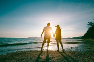 Romantic middle aged couple enjoying beautiful sunset walk on the beach travel vacation, Krabi Thailand