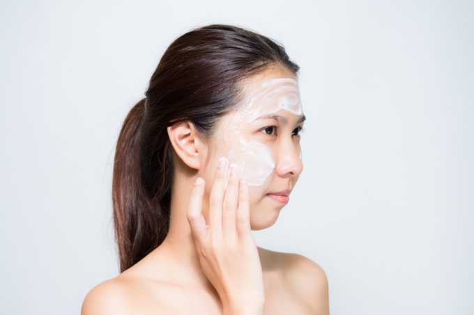 woman applying lotion or mask to face