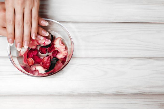 Gentle Natural Manicure, Hand Care. Soaking Finger Nails in Bath with Herbal Oil and Floral on White Wooden Table with Copy Space