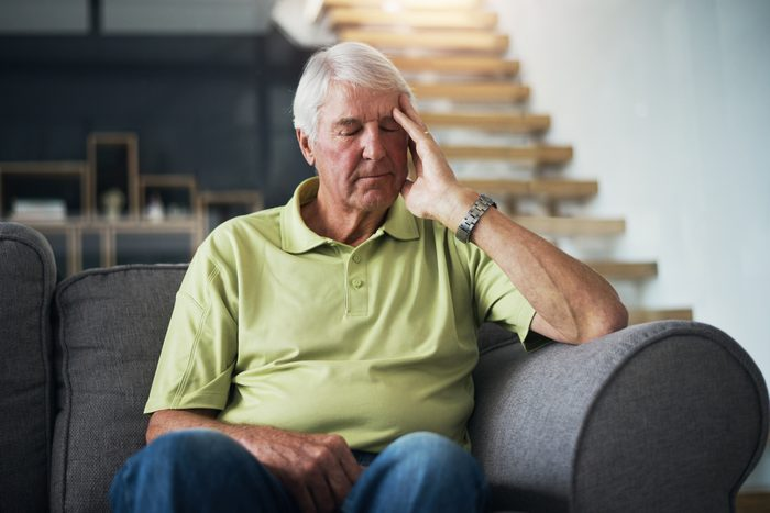 man feeling unwell on couch at home