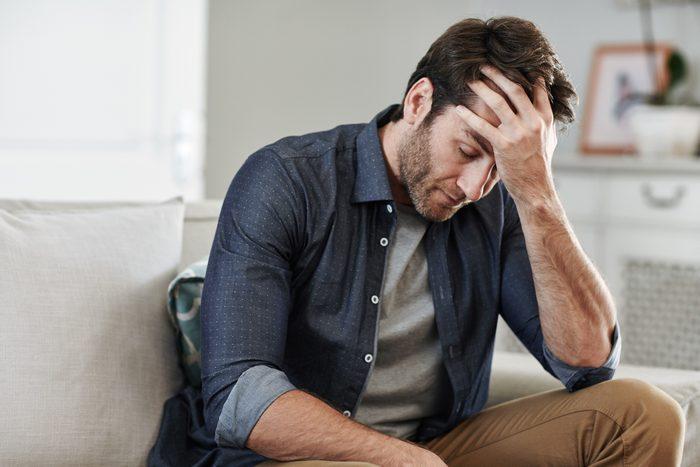 man sitting at home upset