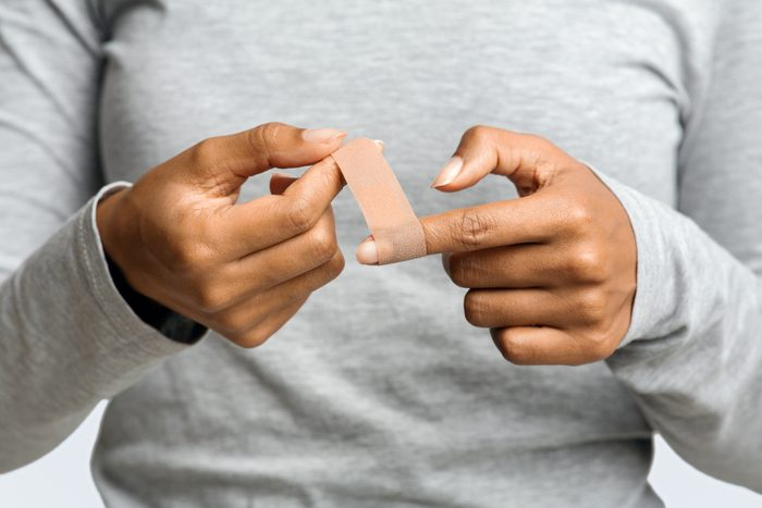 close up of woman putting bandage on finger
