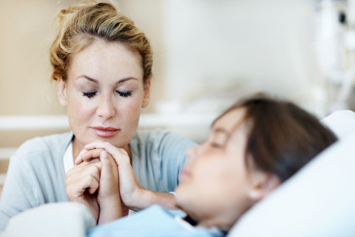 mother sitting with daughter laying in hospital bed