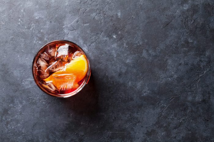 Negroni cocktail on dark stone table. Top view with space for your text